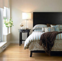 First Light (F1 Online) - Bedroom with blue and brown bedding, bedside table and hydrangeas in vase, Victoria, British Columbia