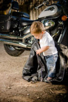 First Light (F1 Online) - Small child holding Leather Jacket beside Motorcycle, outdoor setting