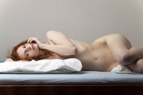 Naked woman lying in bed of artist Bernd Jürgens as framed image
