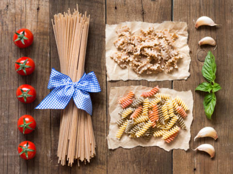 Pasta, tomatoes,garlic and basil on wooden background of artist Ekaterina Fedotova as framed image