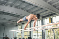 Volodymyr Melnyk - Male gymnast performing handstand on parallel bars