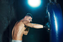 Volodymyr Melnyk - Male boxer boxing in punching bag with dramatic edgy lighting in a dark studio
